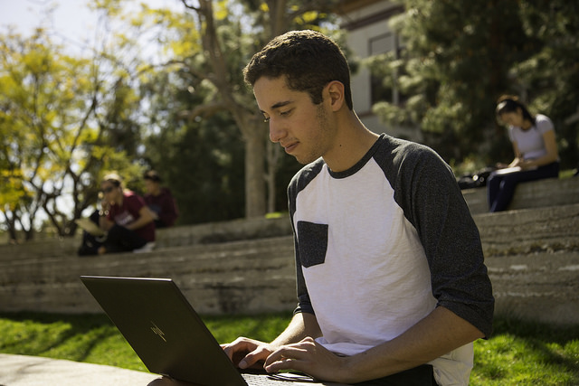 Male student sitting outside working on his laptop
