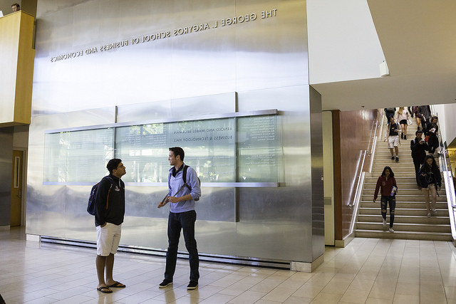 Image of students walking around in the background of the lobby of Beckman Hall, the business school building at 正规赌博网